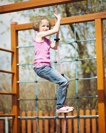 Rope : Young girl climbing rope in playground