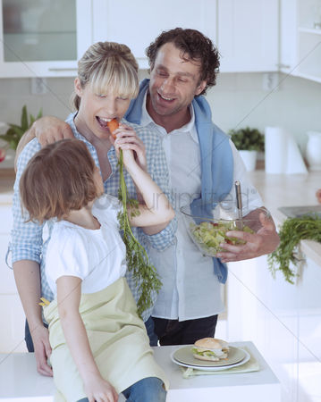 Proud : Young girl eating carrot with parents