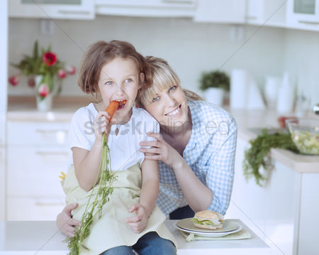 Proud : Young girl eating carrot