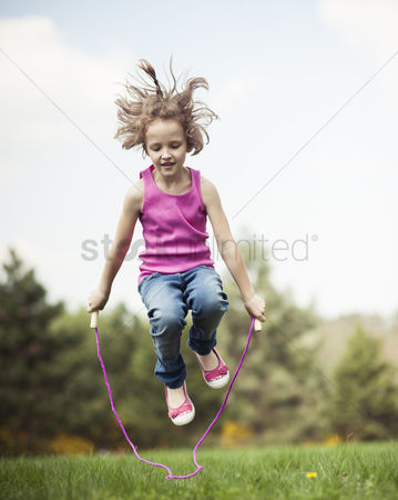 Excited : Young girl skipping in park