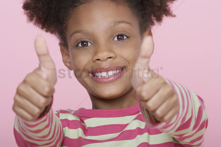 Arm raised : Young girl smiling giving thumbs up