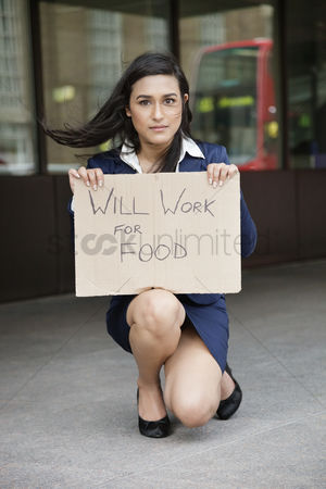 Unemployment : Young indian businesswoman holding  will work for food  sign