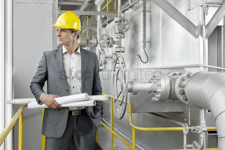 Supervisor : Young male architect holding rolled up blueprints by industrial machinery