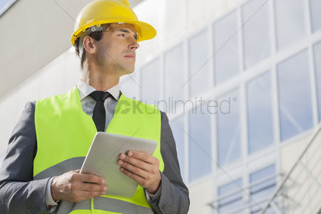 Business suit : Young male architect with digital tablet looking away outside building