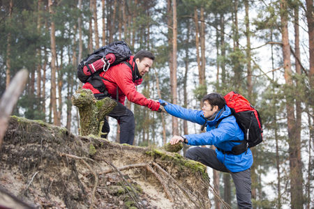 Winter : Young male hiker helping friend while trekking in forest