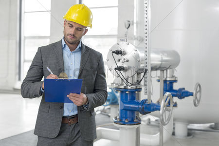 Supervisor : Young male manager writing on clipboard in industry