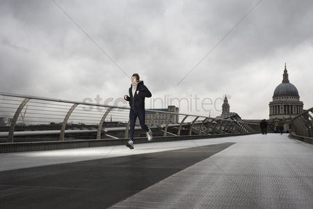England : Young male runner on the millenium bridge with st paul s in the background