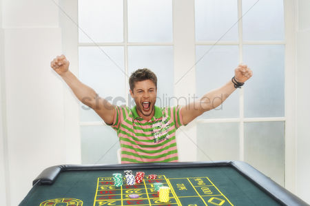 Celebrating : Young man celebrating on roulette table