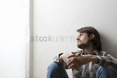 White hair : Young man in checked shirt sits with hands clasped against a wall