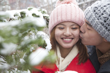 Kissing : Young man kissing young woman in park in snow