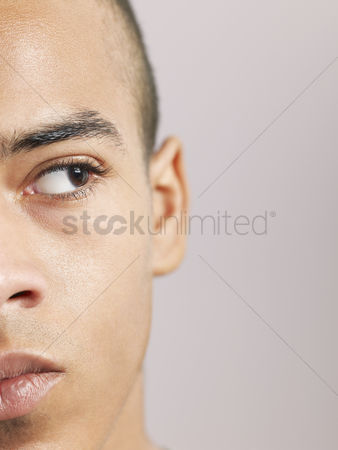 Sullen : Young man looking to side close-up of face  cropped