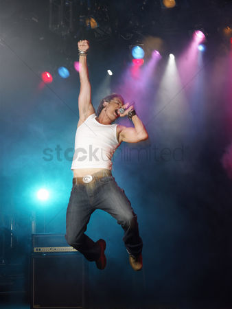 Arts : Young man singing and jumping on stage at concert low angle view