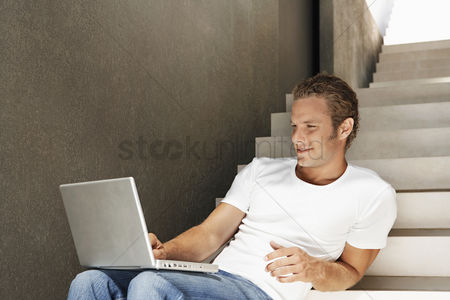 Stairs : Young man sitting on stairs using laptop portrait