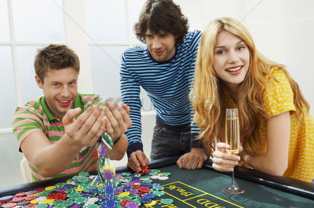 Celebrating : Young man with friends at roulette table playing with chips portrait