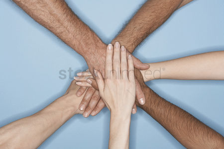 Blue background : Young men and women piling hands on top of each other close-up on forearms and hands