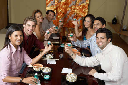 Toasting : Young people toasting with saki cups in japanese restaurant