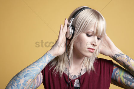 Individuality : Young tattooed woman listening to music on headphones
