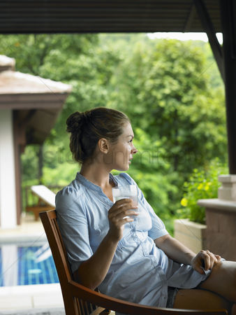 Comfy : Young woman beneath veranda with glass of water