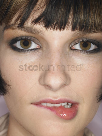 Shyness : Young woman biting lip