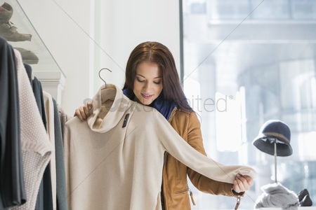Jacket : Young woman choosing sweater in store