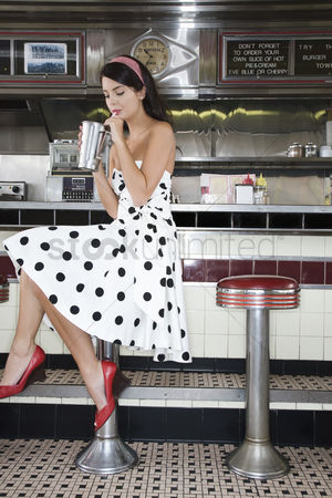 Beautiful people : Young woman drinking a shake in a diner