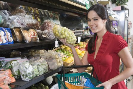 Grapes : Young woman food shopping in supermarket