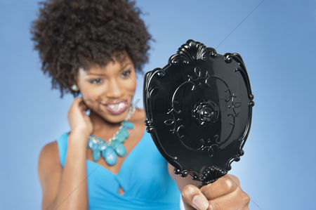 Curly hair : Young woman holding looking at mirror over colored background