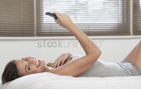 Resting : Young woman holding mobile phone lying on bed