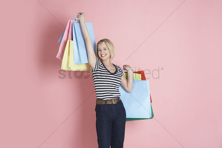 Shopping background : Young woman holding shopping bags and smiling