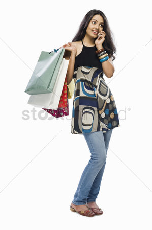 Spending money : Young woman holding shopping bags and talking on a mobile phone