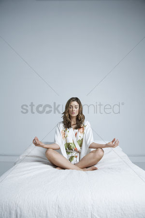 Floral : Young woman in dressing gown meditating in bed
