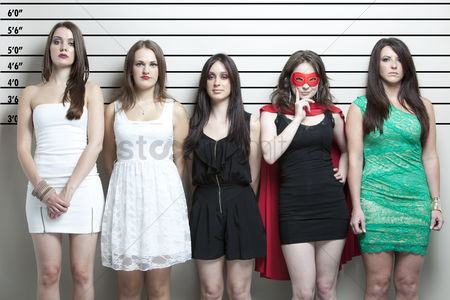 Group portrait : Young woman in superhero costume with friends in a police lineup