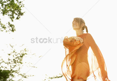 Dancing : Young woman in swimsuit dancing with transparent robe in park low angle view