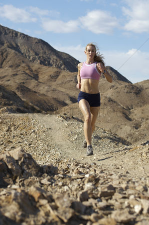 Landscape : Young woman jogging in mountains
