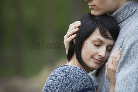 Head shot : Young woman laying head on chest of young man
