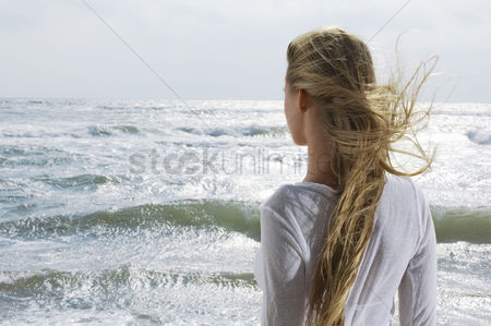 Contemplation : Young woman looking at ocean back view