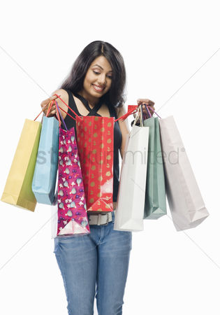 Spending money : Young woman looking into a shopping bag