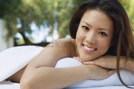 Club : Young woman lying on massage table outdoors portrait