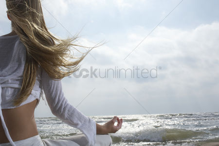 People : Young woman meditating on beach facing ocean back view