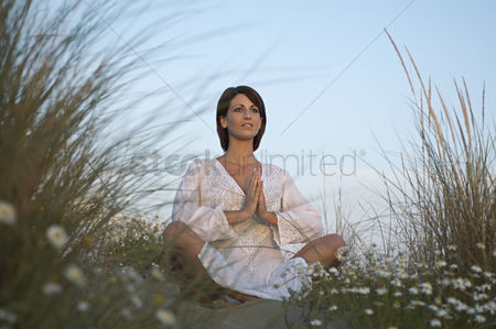 Grass : Young woman meditating on sand dune