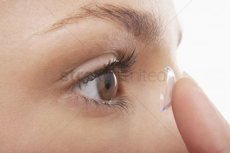 Vision : Young woman putting in contact lens