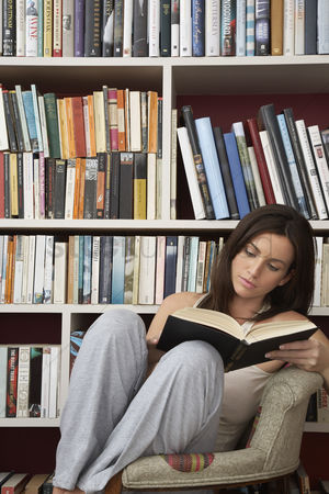 Knowledge : Young woman reading in chair by bookshelf