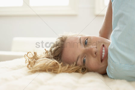 Arm raised : Young woman relaxing on bed portrait