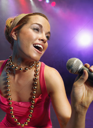 Arts : Young woman singing on stage in concert close up low angle view