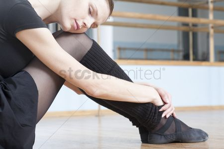 Dance : Young woman sits resting in rehearsal room