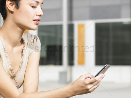Cell phone : Young woman sitting in plaza sending text message close up