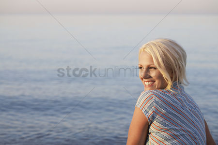 Ponytail : Young woman sitting on beach side view