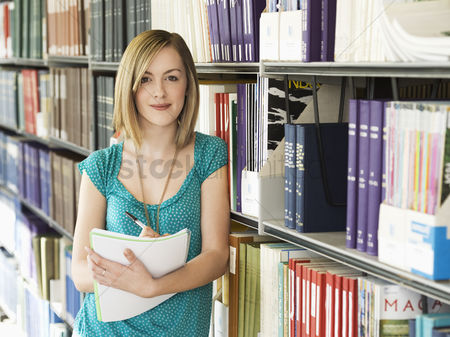 College : Young woman standing by bookshelf in library taking notes