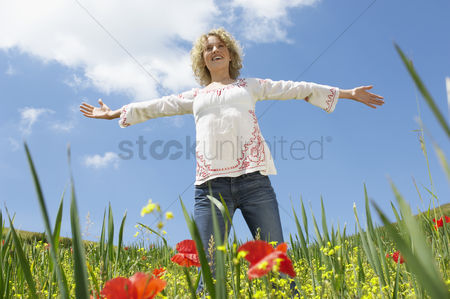 Curly hair : Young woman standing in field with open arms low angle view front view