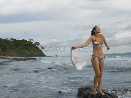 Gladness : Young woman standing on rock at beach